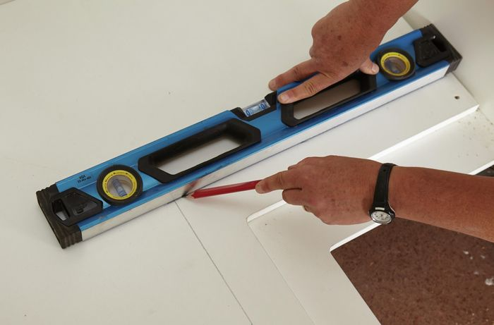 A person using a spirit level as a straight edge to draw a line on a cabinet panel