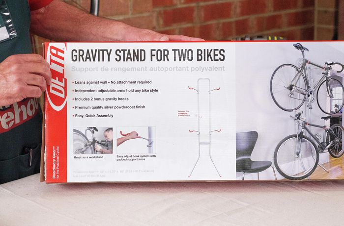 """Person holding a box with the label """"Gravity stand for two bikes"""""""