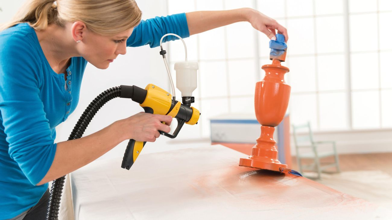 lady using a spray gun to paint a lamp base in orange paint