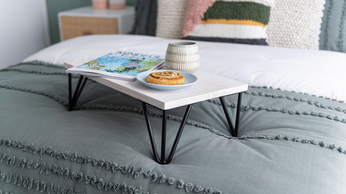 White painted bed tray topped with a magazine, danish on a plate and mug on a made up bed
