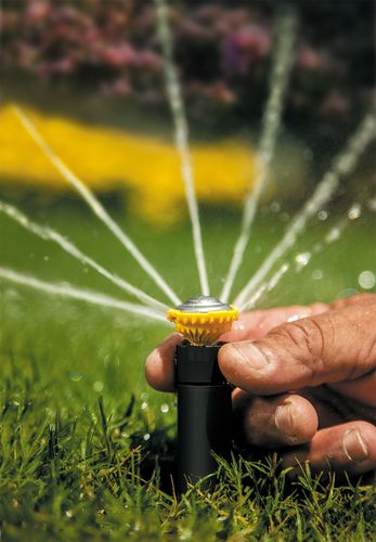 Close up of person adjusting a sprinkler head with water spraying out