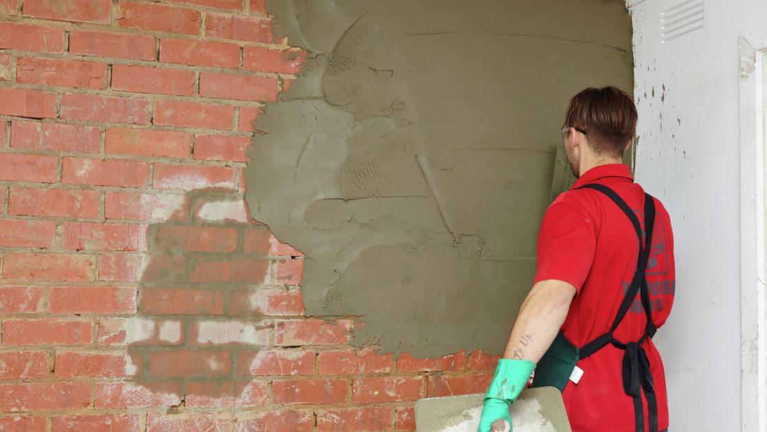 A person applying cement plaster to a brick wall using a trowel
