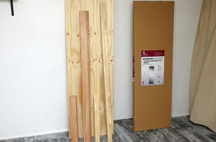 Lengths of timber and plywood and a sliding wardrobe mirror door in packaging