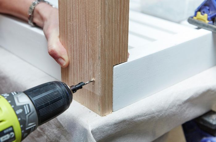 Person drilling hole into table leg and tabletop