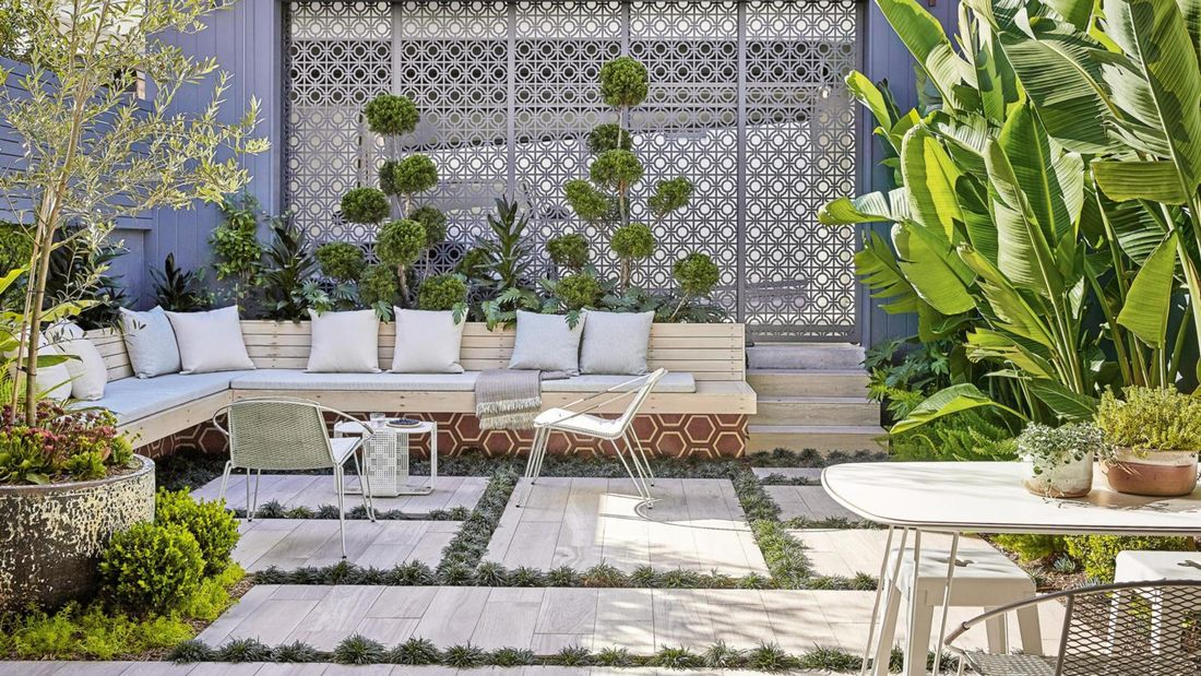 An outdoor room with timber bench seats, concrete pavers, metal wall screens and green plants