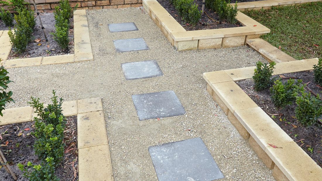Five stepping stone pavers set into a gravel path