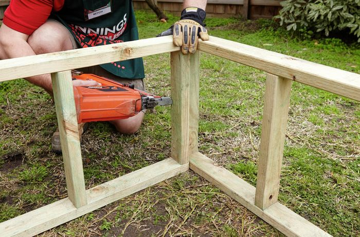 Supports for the roosting box being nailed together by a Bunnings team member with a nail gun