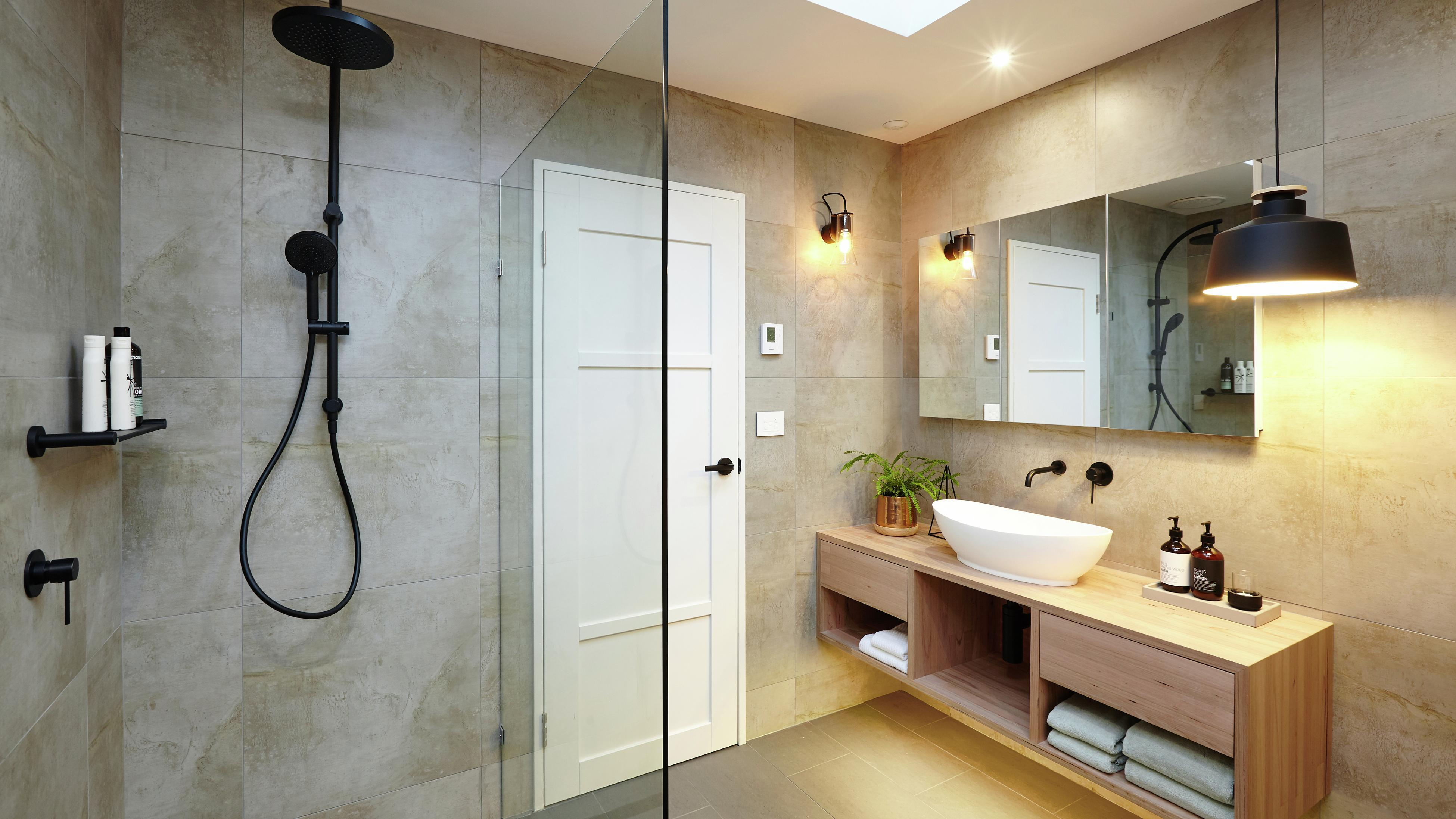 Bathroom with earthy tiles and black tapware/accessories.