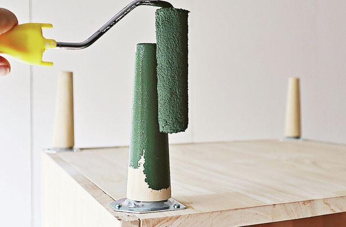 Close up of a person using a paint roller to paint bedside table legs green