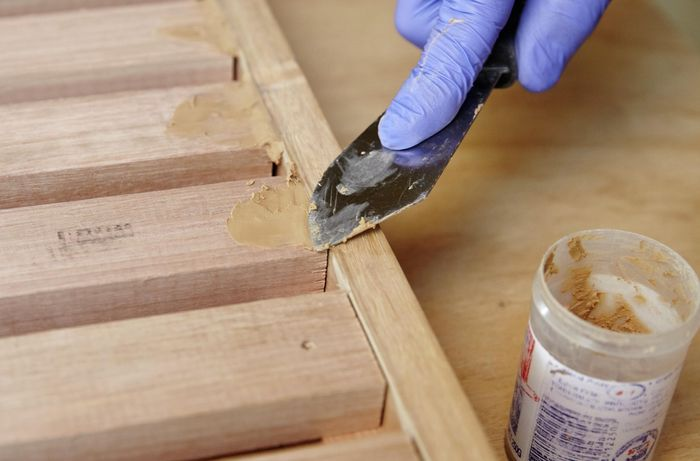 Person using putty to fill cracks in timber joins