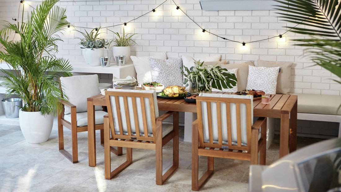 A finished party space with hanging lights, pot plants, and a dining setting loaded with food
