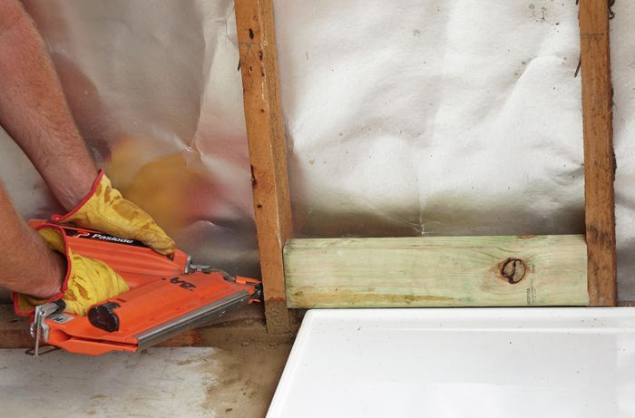 Nogs being fitted to the inside of a wall frame and nailed down with a nail gun