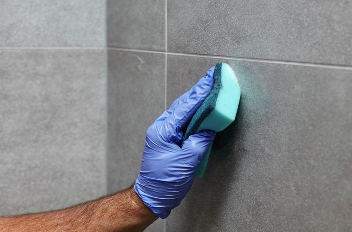 Tiles being cleaned before a grout sealing with a sponge and protective gloves