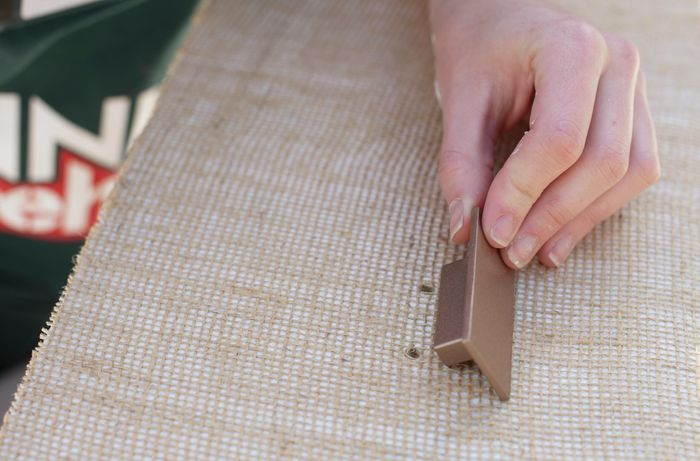 Person attaching a handle to a drawer covered in hessian