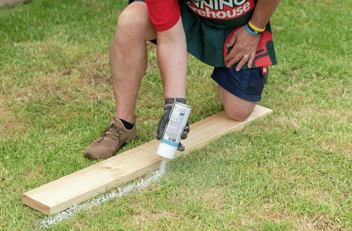 Bunnings team member spray painting a line with a piece of timber as a guide