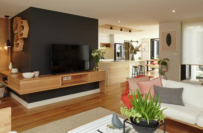 An open plan living room with television, lounge and coffee table