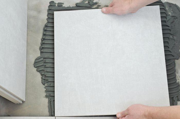 Close up of a person placing a tile against wet concrete