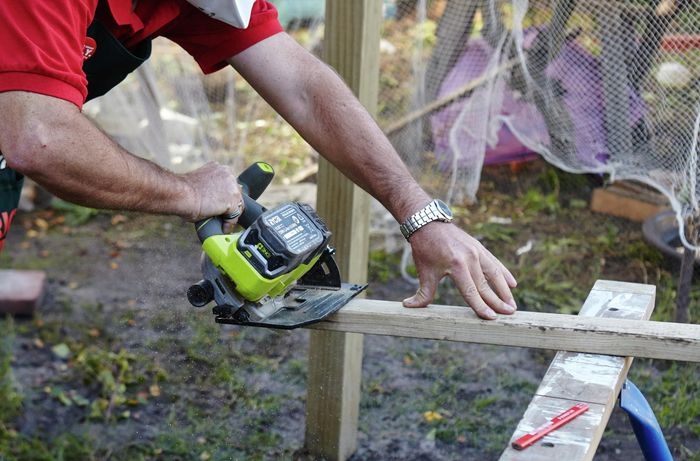 Person sawing bit of timber.