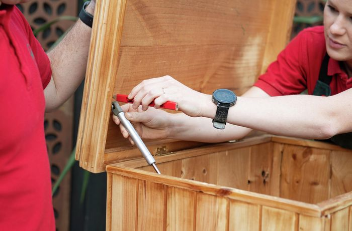 Person marking a screw hole on the underside of a chest lid