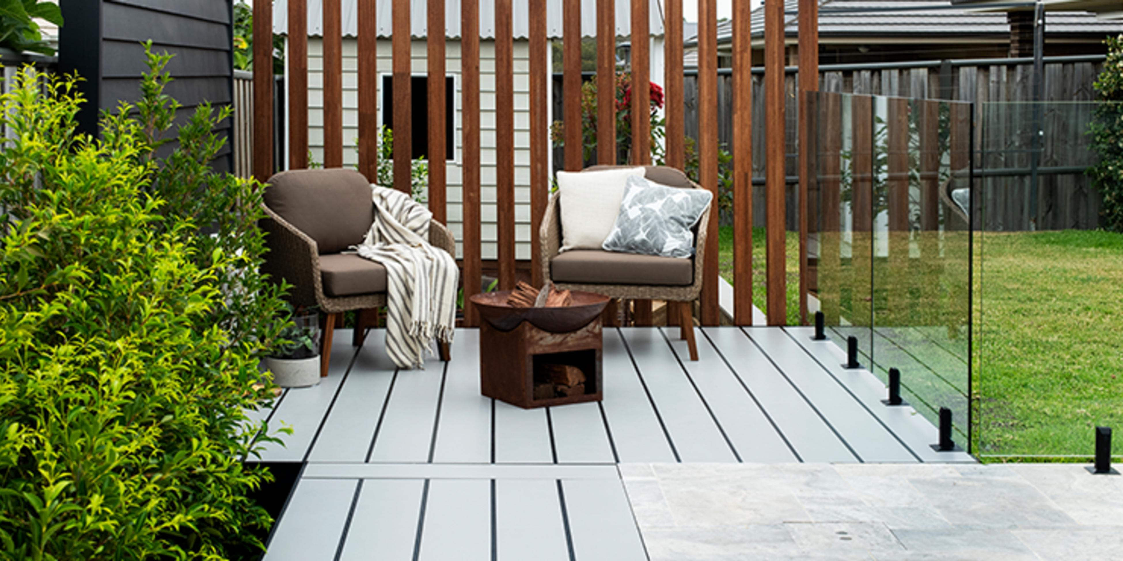 Pool surrounded by timber decking with two chairs and a firepit