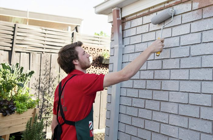 Person painting brick wall with a paint roller.