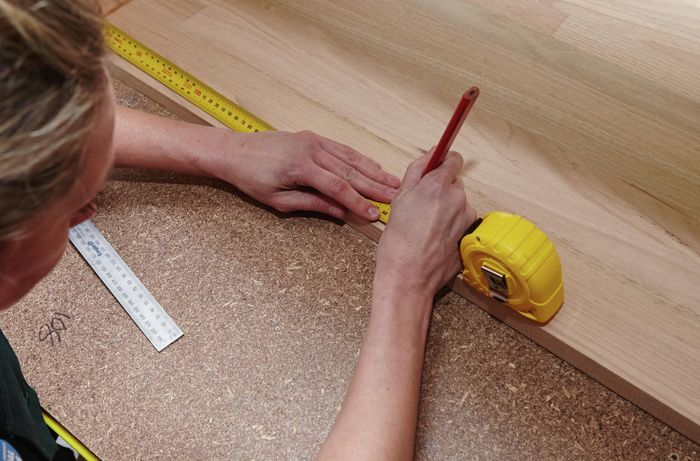 A person marking a measurement onto a timber panel using a measuring tape