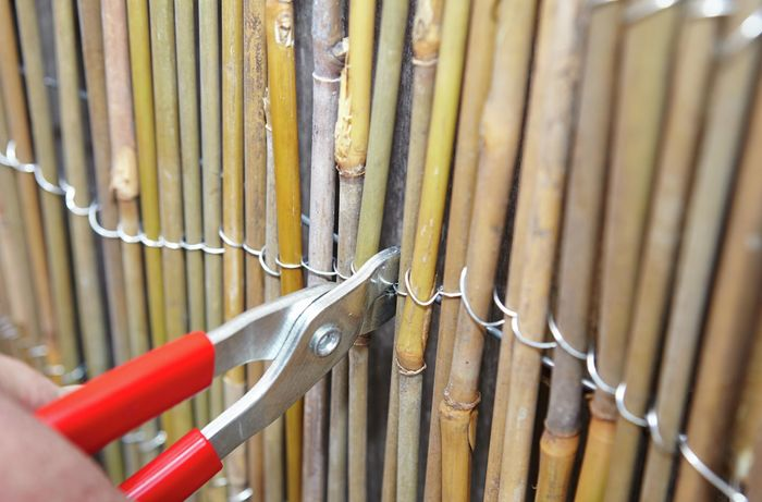 A person using a crimping tool to attach bamboo screen to a paling fence