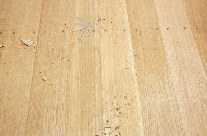 A hardwood timber floor covered with dust and debris