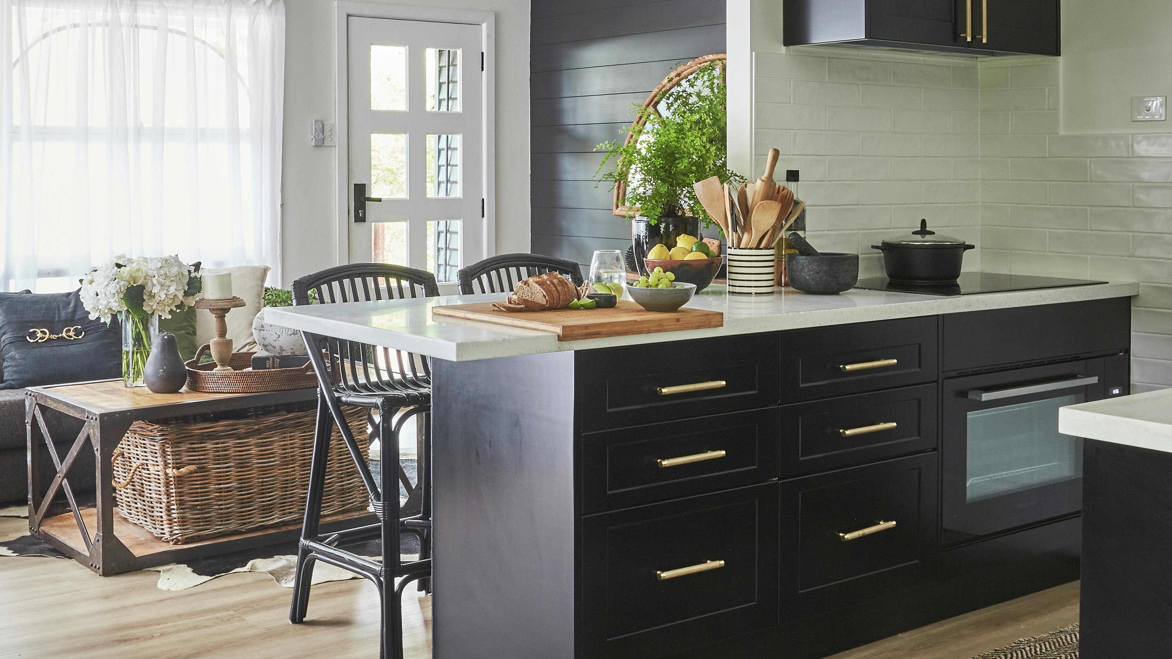 Modern monochrome kitchen with black cabinetry with gold coloured handles and timber look floorboards