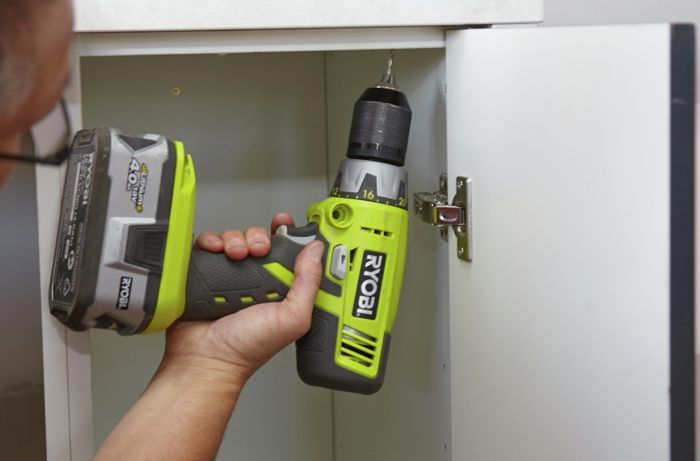 Person screwing benchtop and cabinet together