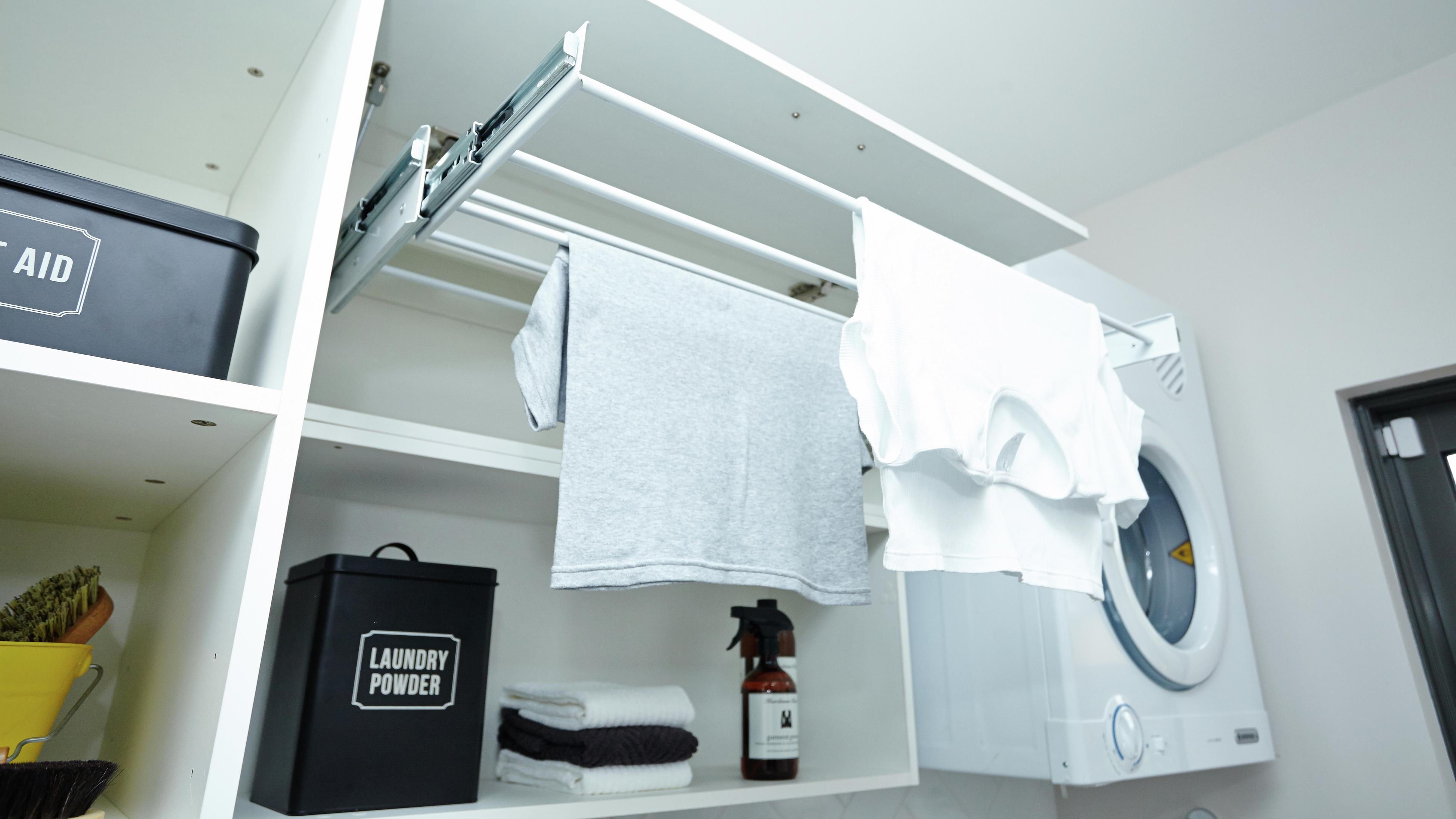 A drying cupboard with two tee shirts hanging on the drying rack.