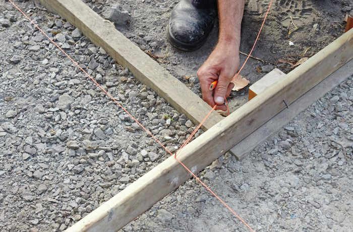 Person wrapping string around timber.