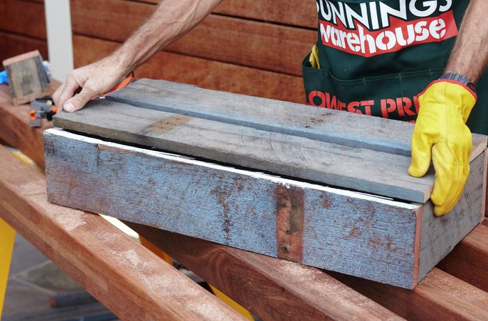 The base of a planter box being put into place by a Bunnings team member
