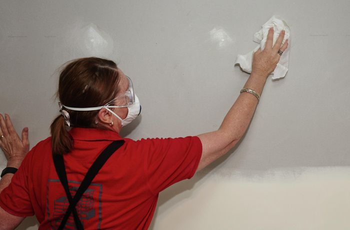 A wall being wiped clean before being given an undercoat