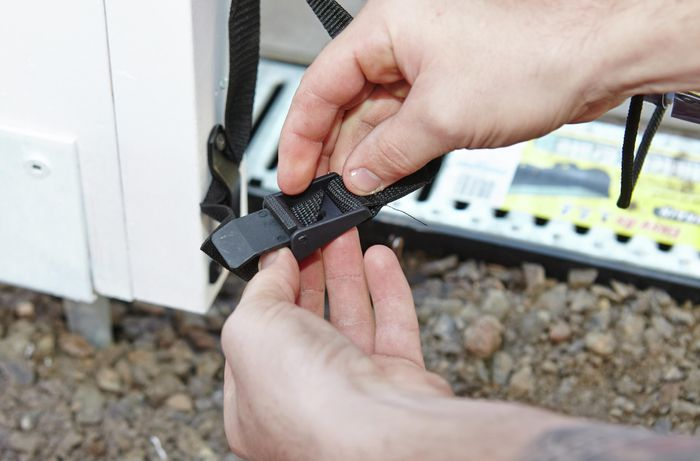 A person adjusting an anchor belt with a plastic clip