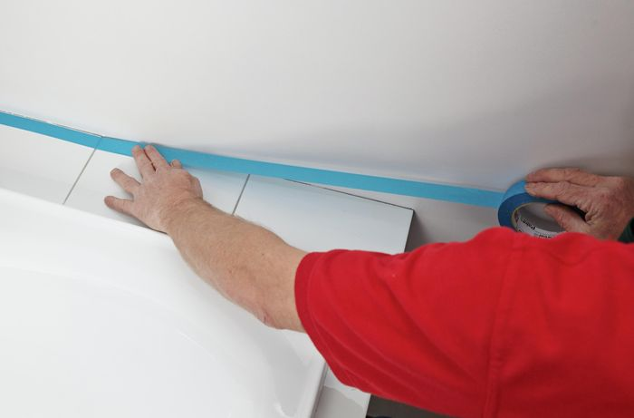 A person applying masking tape along the edge of a bath hob