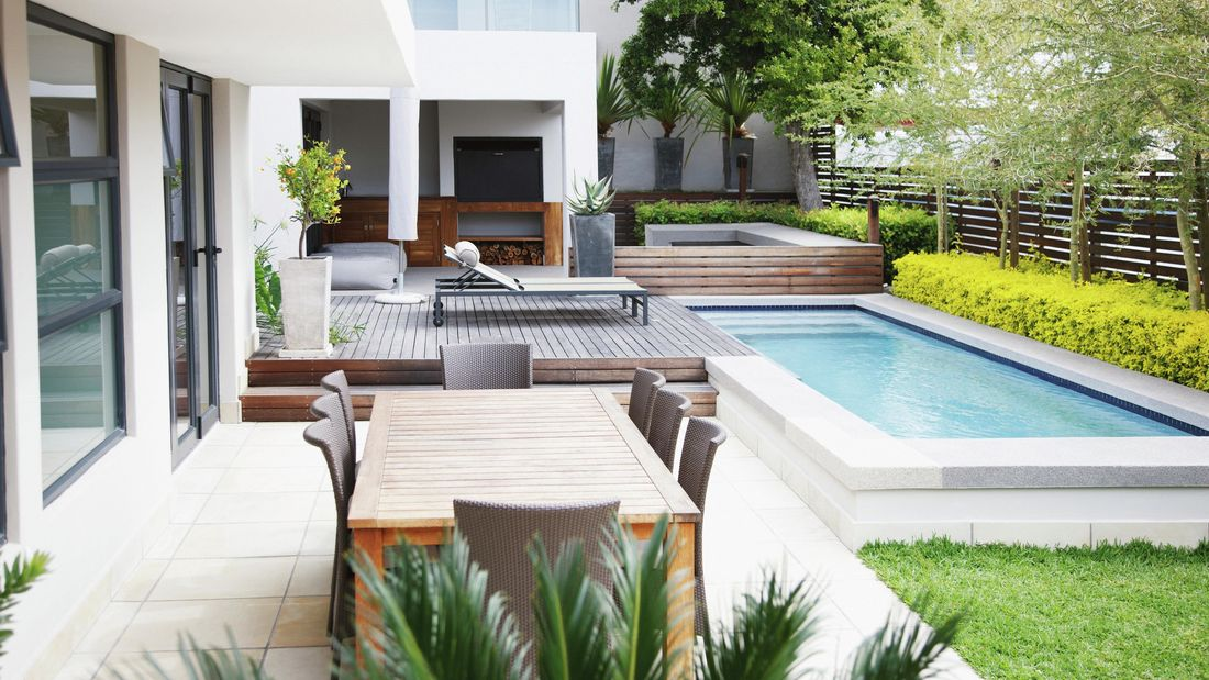 A large backyard area with wooden dining table, deck, sunbed, pool and plants