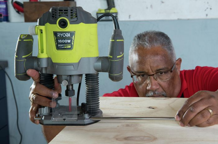 Person attaching router to center anchor point of timber