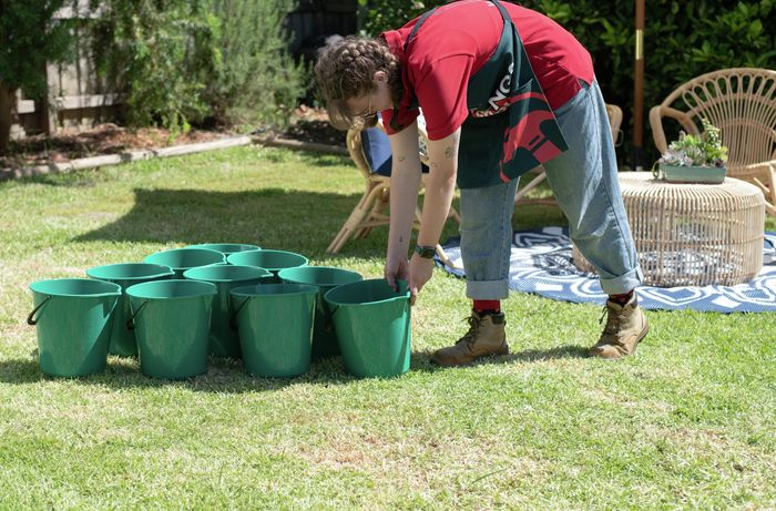 Person lining up green buckets into a triangle.