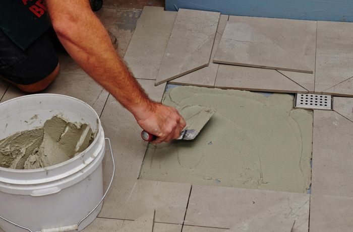 A person using a trowel to spread adhesive on a shower base