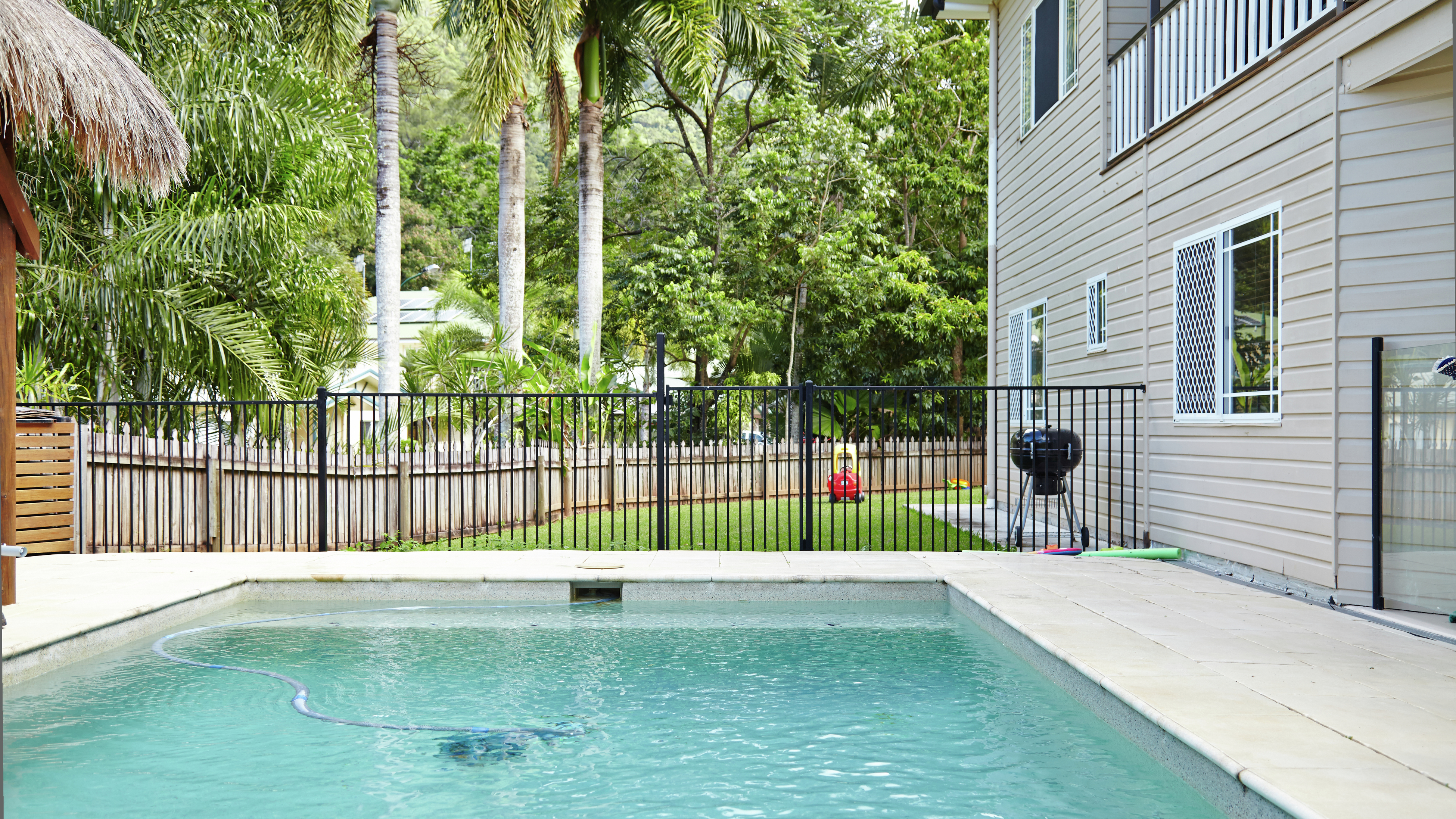 A pool surrounded by pool fencing outside a house