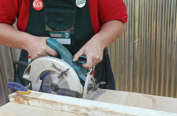 A person cutting plywood with a circular saw