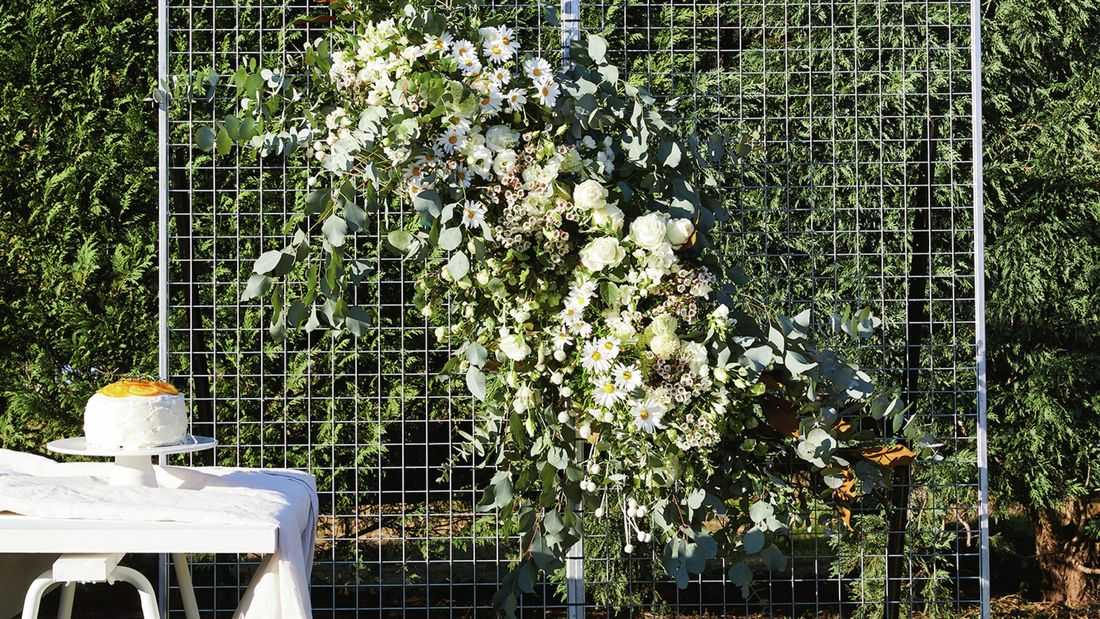 A floral wall made from wire panels adorned with white flowers.