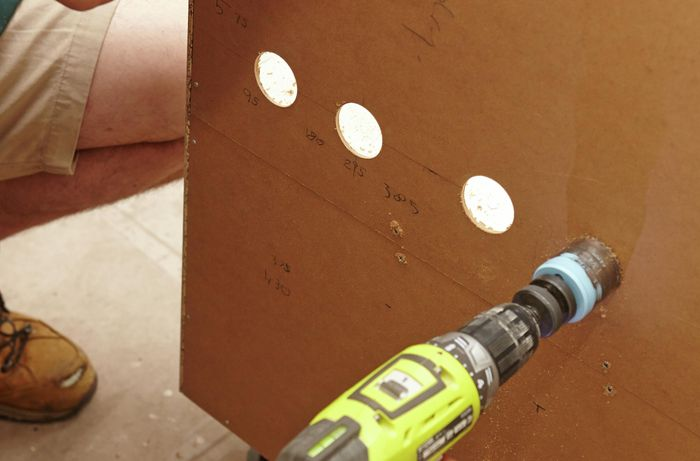 Cutting the pipe holes in the laundry cabinet with a hole saw.