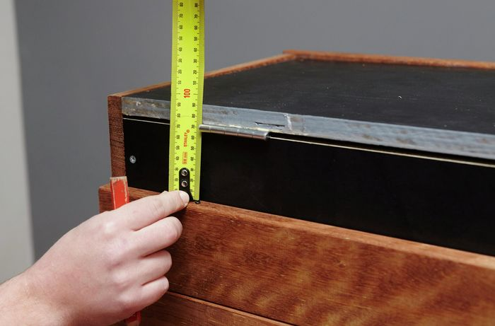 A person measuring a bench seat