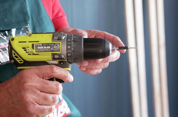 A drill being used to mark holes in a flat wooden panel