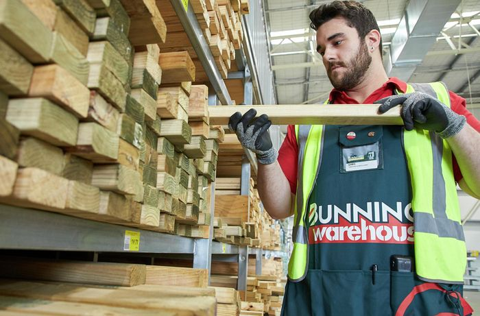 team member stacking treated pine framing timber