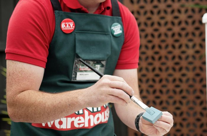 A square toggle being painted pale blue by a Bunnings team member with a paintbrush