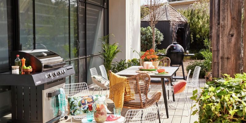 Outdoor entertaining area including a deck, outdoor table and chairs, and a barbecue.