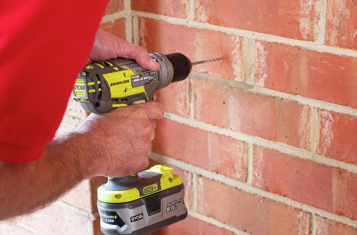 Person drilling a hole in a brick wall with a cordless drill